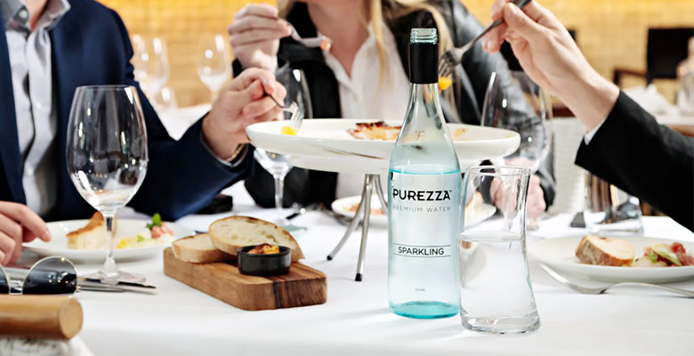 Customers eating food in a restaurant being served purezza sparkling water